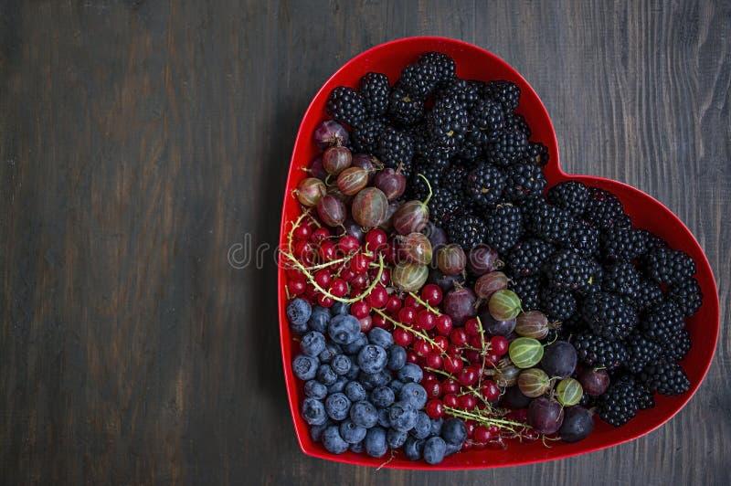 Reeks verse vruchten braambessen, kruisbessen, rode aalbessen, bosbessen in een rode hartdoos Vruchten voor de Dag van Valentine  stock fotografie
