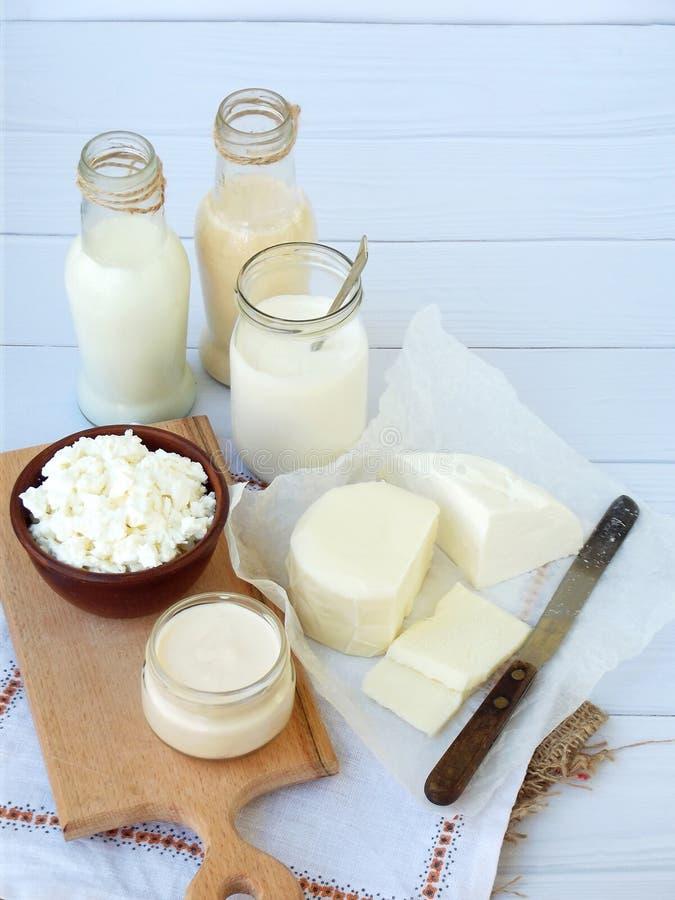 Reeks verse zuivelproducten op houten achtergrond: melk, kaas, plattelandshuisje, yoghurt, ei, mozarella, ryazhenka, feta stock foto's