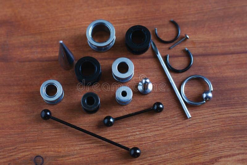 Reeks voor het doordringen van Doordringende toebehoren op houten achtergrond een catheter voor de tong een staaf in de tong en d stock foto's