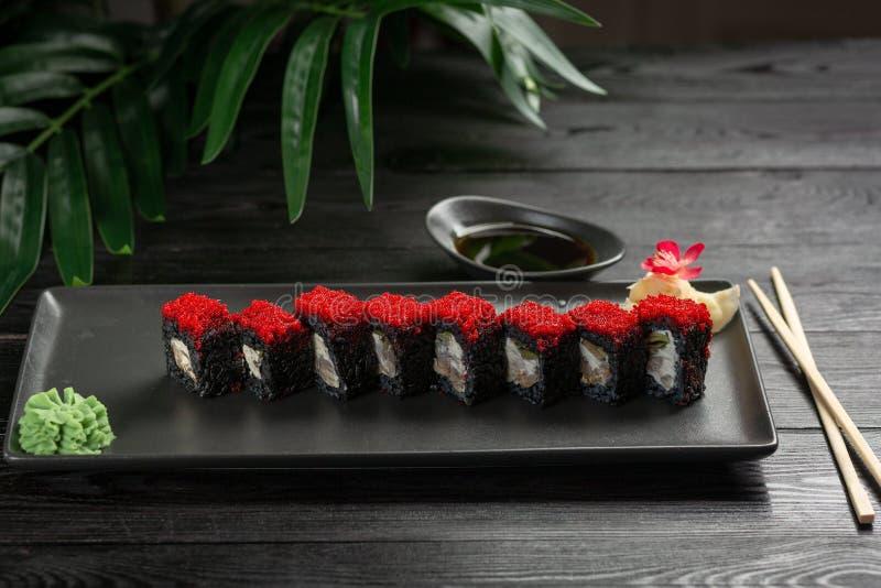 reeks zwarte sushibroodjes op een zwarte plaat op een zwarte houten achtergrond royalty-vrije stock afbeeldingen