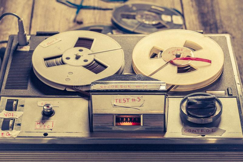 Reel audio recorder with a few rolls of tape. On old table stock photo