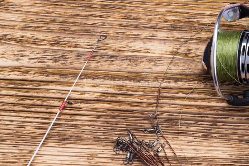 Reel with fishing line from fishing pole lies on a wooden burnt background royalty free stock photography