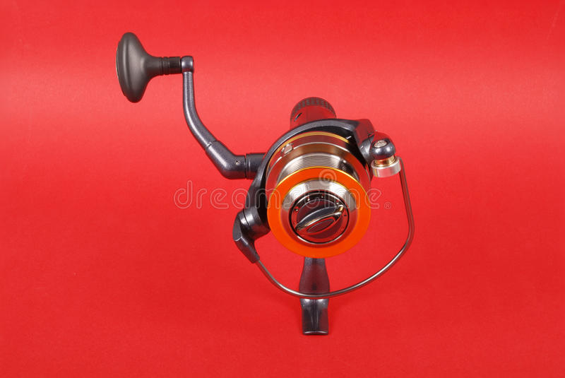 Reel for fishing rods. Close up on red background royalty free stock image