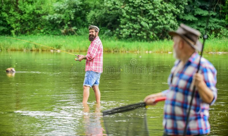 Reel friendship. two fishermen with fishing rods, selective focus. mature man fisher. hobby and sport activity. son and. Reel friendship. two fishermen with stock images