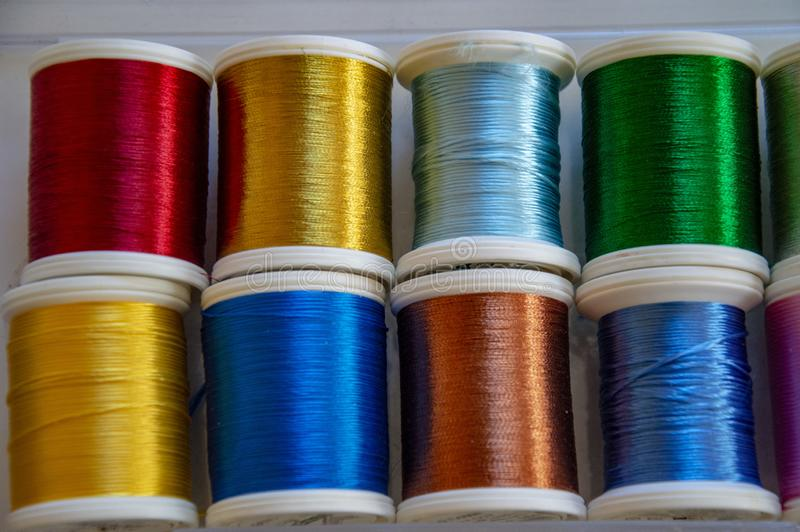 Reels of colored threads for needlework and sewing. Yellow, green, blue royalty free stock image