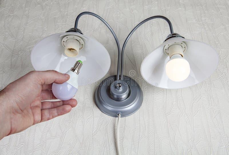 Reemplazo de las bombillas eléctricas en lámpara de pared del hogar, bombilla del LED imágenes de archivo libres de regalías