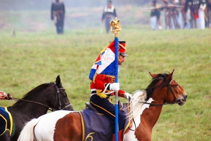 Reenactor si è vestito come il soldato di guerra napoleonica porta una bandiera francese fotografie stock libere da diritti
