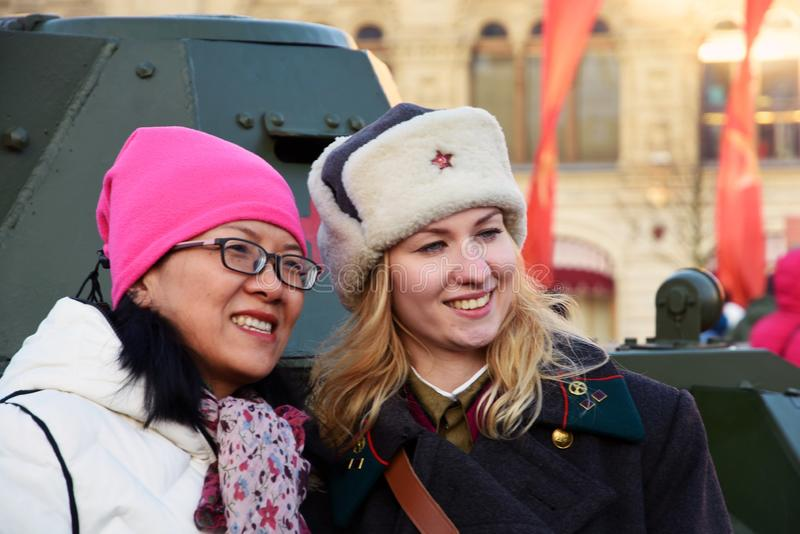 Reenactor woman and Asian tourist on the Red Square. They pose for photos by military equipment of Second World War shown on the Red Square in Moscow on stock photos