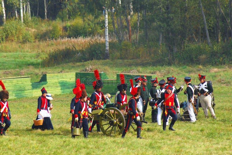 Reenactors vestiu-se como os soldados da guerra de Napoleão estão por um canhão imagens de stock royalty free