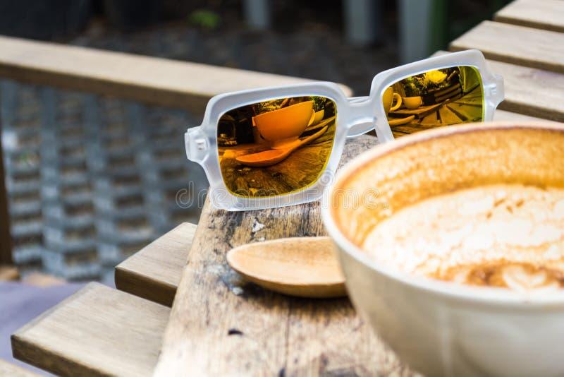 Refection γυαλιών ηλίου του φλυτζανιού καφέ στοκ εικόνες
