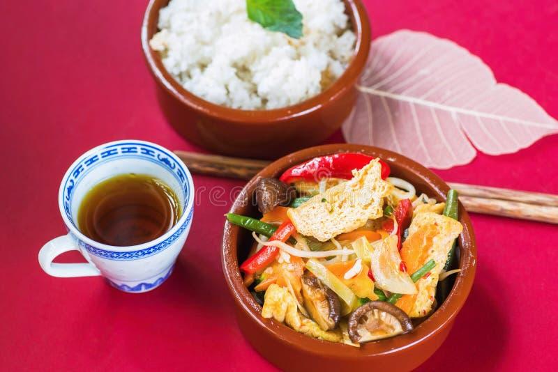 Refeição asiática do vegetariano, tofu fritado, shiitake e vegetal, arroz, chá, hashi no fundo vermelho imagens de stock royalty free