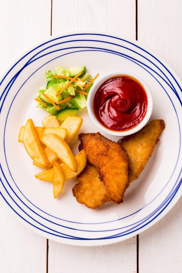 A refeição da criança - tiras, batatas fritas, salada e ketchup do frango frito fotos de stock royalty free