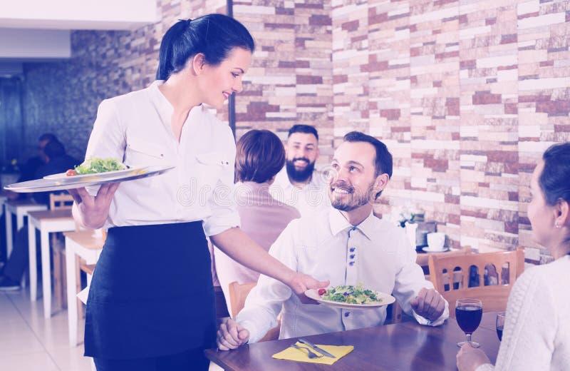Refeição de sorriso do serviço da empregada de mesa para convidados do restaurante fotos de stock royalty free