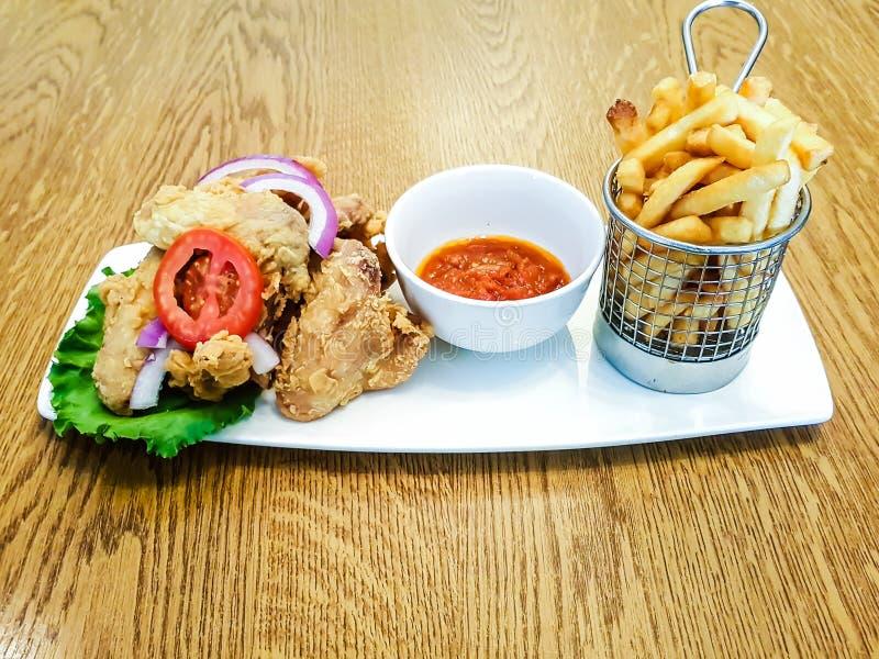 Refeição do fast food do molho do frango frito e de tomate com batatas fritas, microplaquetas de batata em uma cesta imagens de stock royalty free