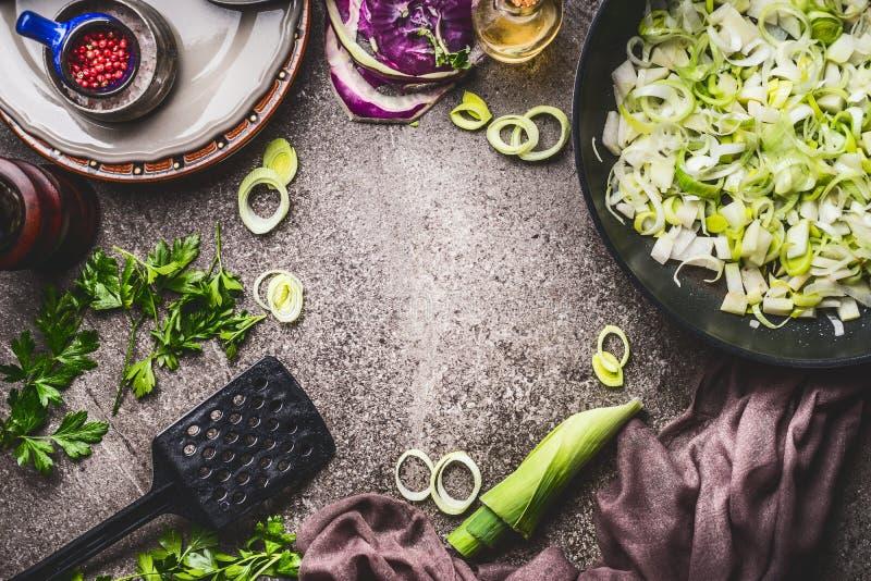 Refeição dos alho-porros que come e que cozinha Bandeja com os alho-porros cortados no fundo da mesa de cozinha com ferramentas e imagens de stock royalty free