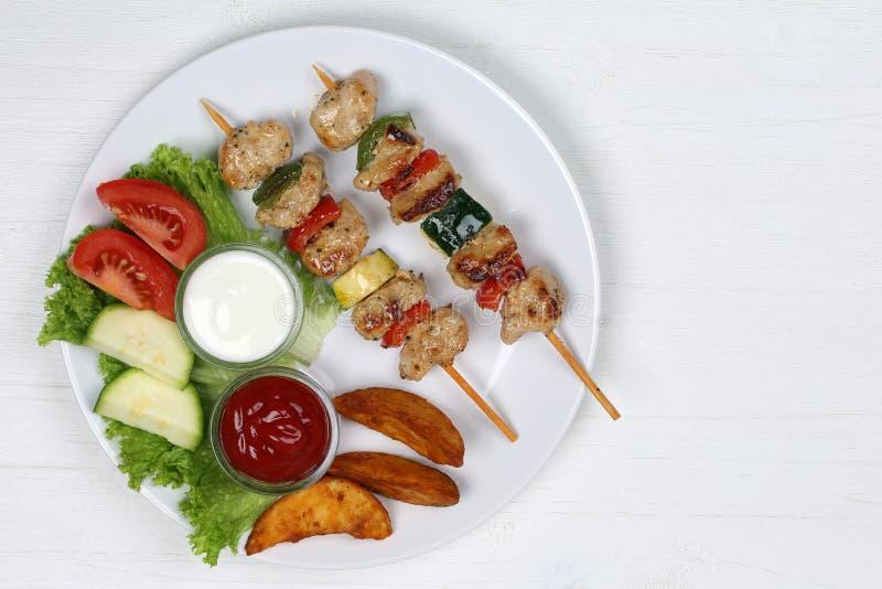 Refeição dos espetos da carne da galinha com batatas e vegetais na placa fotografia de stock