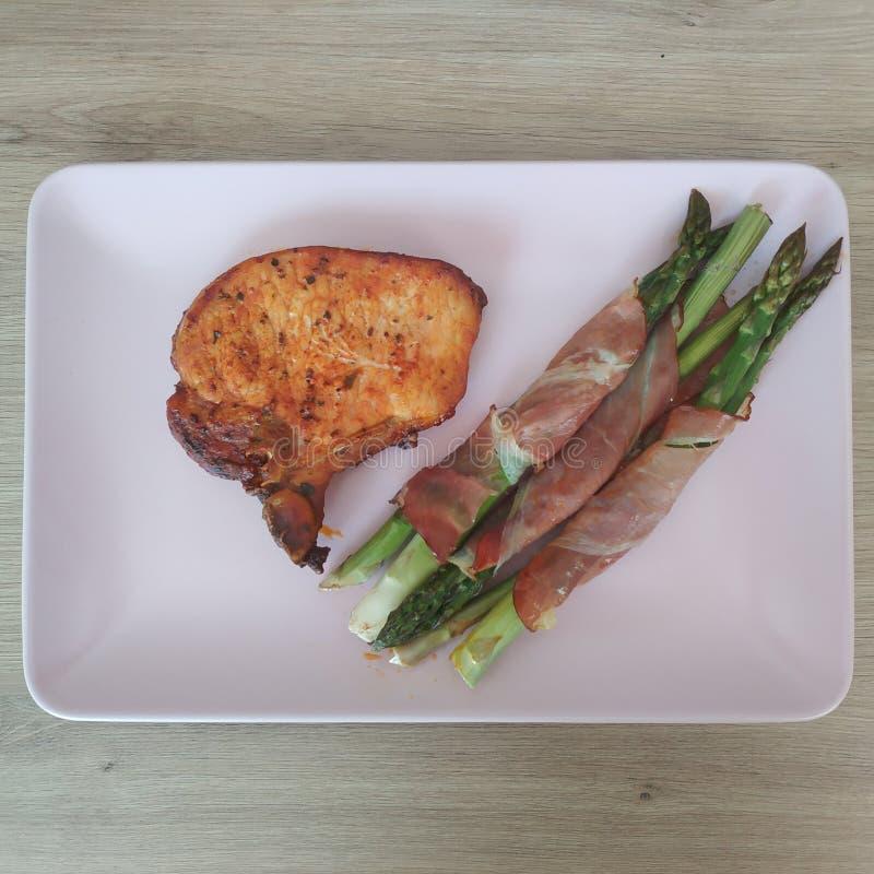 A refeição Ketogenic, costeleta de carne de porco, bacon envolveu o aspargo Perda de peso do alimento do Keto fotografia de stock royalty free