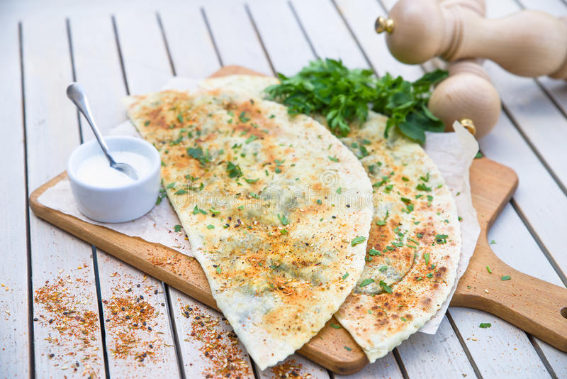 Refeição turca típica Gozleme com erva e queijo na placa de corte de madeira leve imagens de stock royalty free