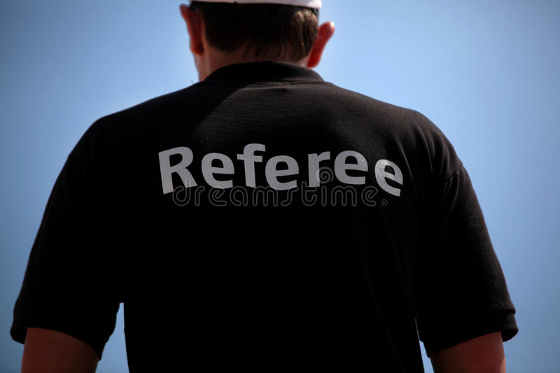 Referee. A referee is observing a volleybal match at the beach royalty free stock photos