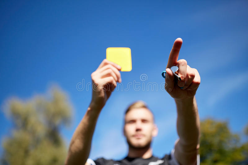 Referee on football field showing yellow card. Sport, caution, game and people - referee with whistle showing yellow card on football field royalty free stock photography