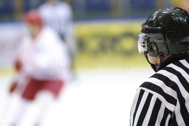 Referee at the hockey match. Hockey sport background - rear view of the referee against the blurry hockey game stock photo