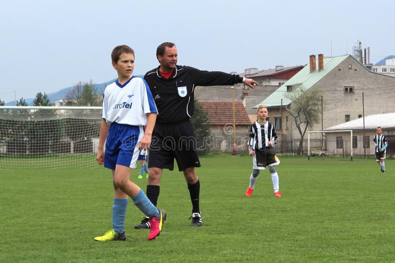 Referee on kids soccer match category U13. Behind player of FK Rajec during match of third Slovakian league in this category. Kids sports life. Soccer referee stock images