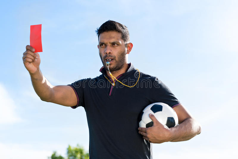 Referee with red card. Portrait of referee with a ball showing red card and whistling stock photos