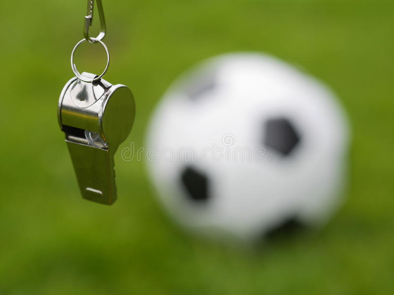 Referee whistle. In front of soccer ball stock images