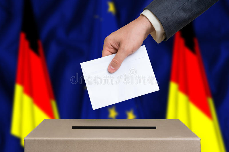 Referendum in Germany - voting at the ballot box. Referendum in Germany. The hand of man putting his vote in the ballot box. Germany and European Union flags on royalty free stock photos