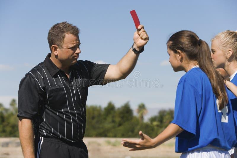 Referent, der den weiblichen Fußball-Spielern rote Karte zeigt stockfotografie