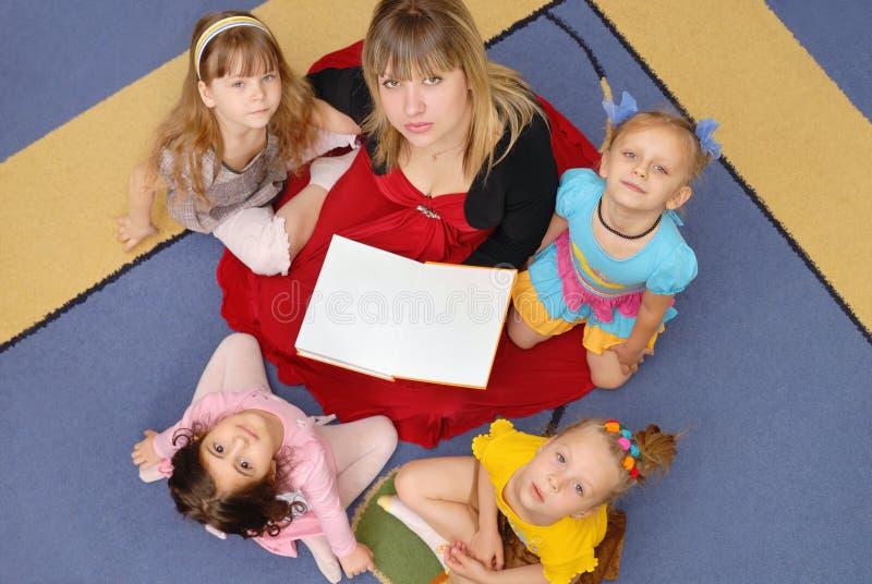 Referent und Kinder in einem Kindergarten stockbild