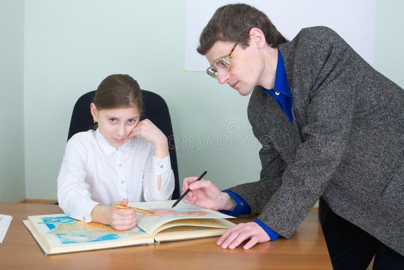 Referent und Schulmädchen mit Atlas stockfotografie