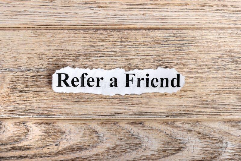REFIERA un texto del AMIGO en el papel La palabra REFIERE A UN AMIGO en el papel rasgado Imagen del concepto imágenes de archivo libres de regalías