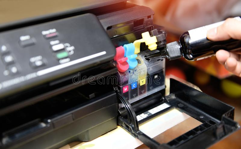 Refill ink tank printer at office - Close up printer cartridge inkjet of color black CMYK and repair fix the problem concept , stock photography
