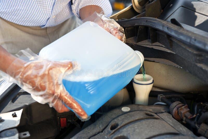 Refilling windscreen wiper fluid royalty free stock image