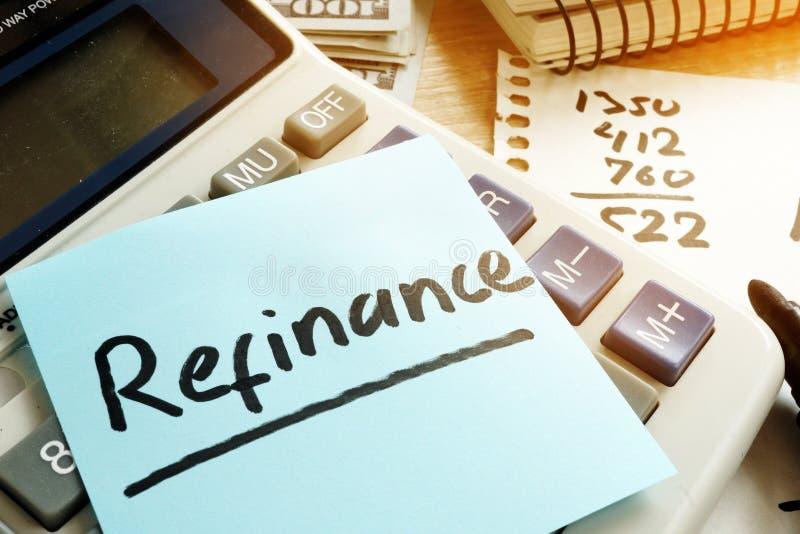 Refinance escrito em uma vara e em uma calculadora do memorando fotografia de stock royalty free