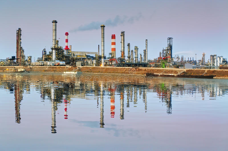 Refinaria de petróleo na noite com reflexão na água imagens de stock