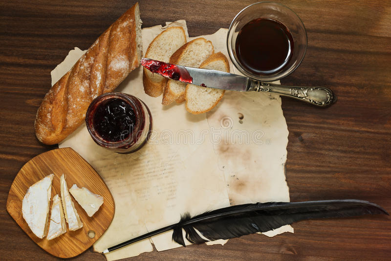 Refined still life of red wine glass, camembert cheese, baguette. Still life in retro style with glass of red dry wine, fresh baguette bread, sliced camambert or stock images