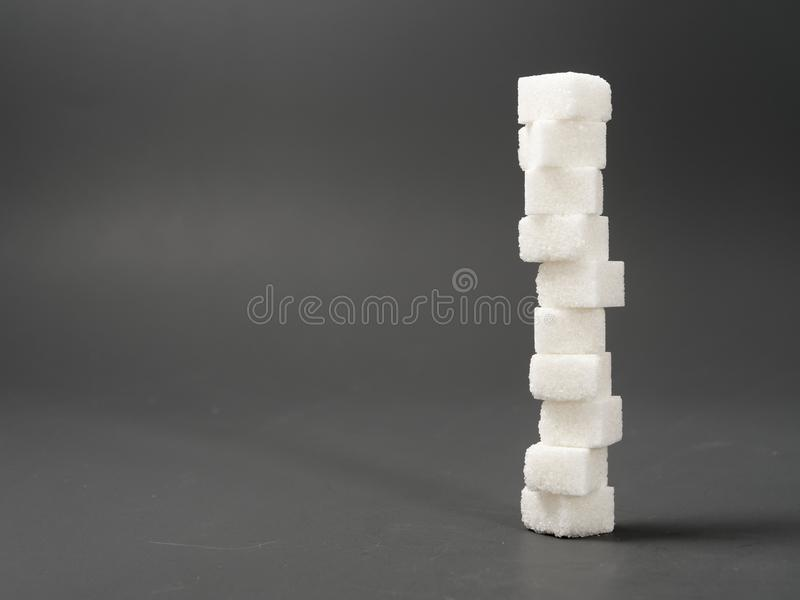 Refined sugar lump white and cane on a gray background. Refined white sugar cubes with stevia pills on grey background royalty free stock photography