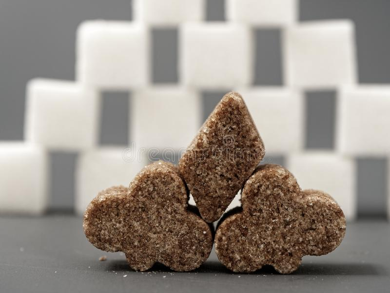 Refined sugar lump white and cane on a gray background. Refined white sugar cubes with stevia pills on grey background royalty free stock image
