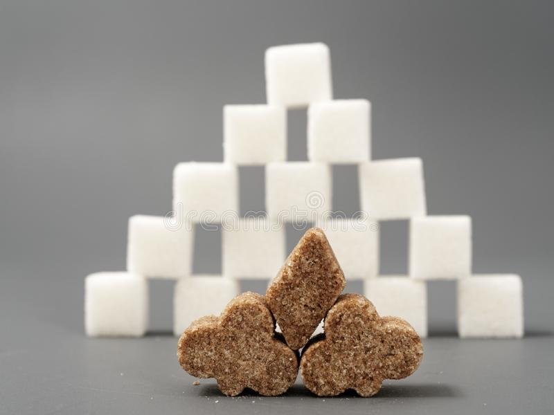 Refined sugar lump white and cane on a gray background. Refined white sugar cubes with stevia pills on grey background stock image