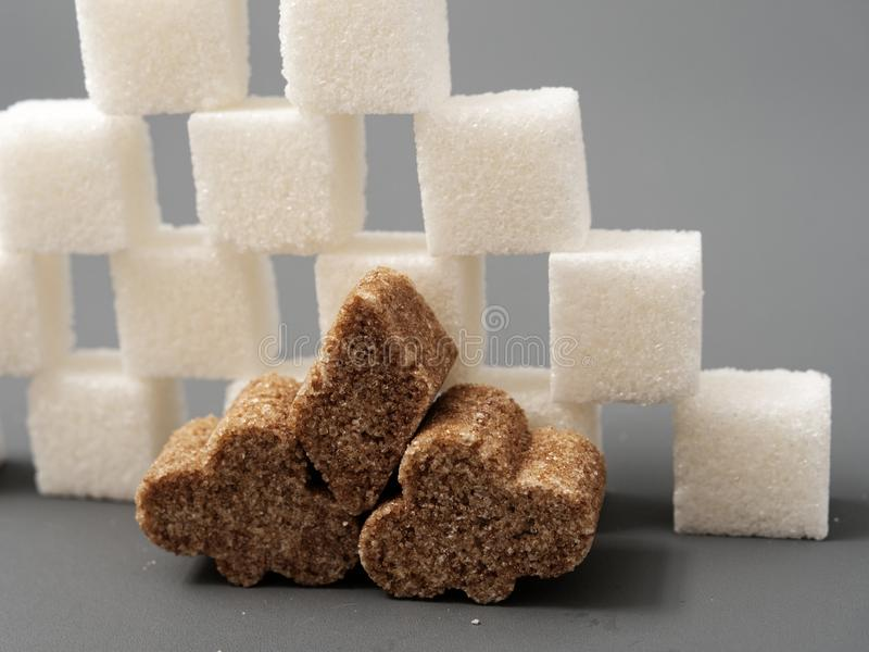 Refined sugar lump white and cane on a gray background. Refined white sugar cubes with stevia pills on grey background royalty free stock photo