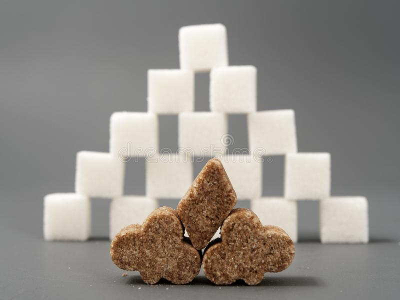 Refined sugar lump white and cane on a gray background. Refined white sugar cubes with stevia pills on grey background stock photography
