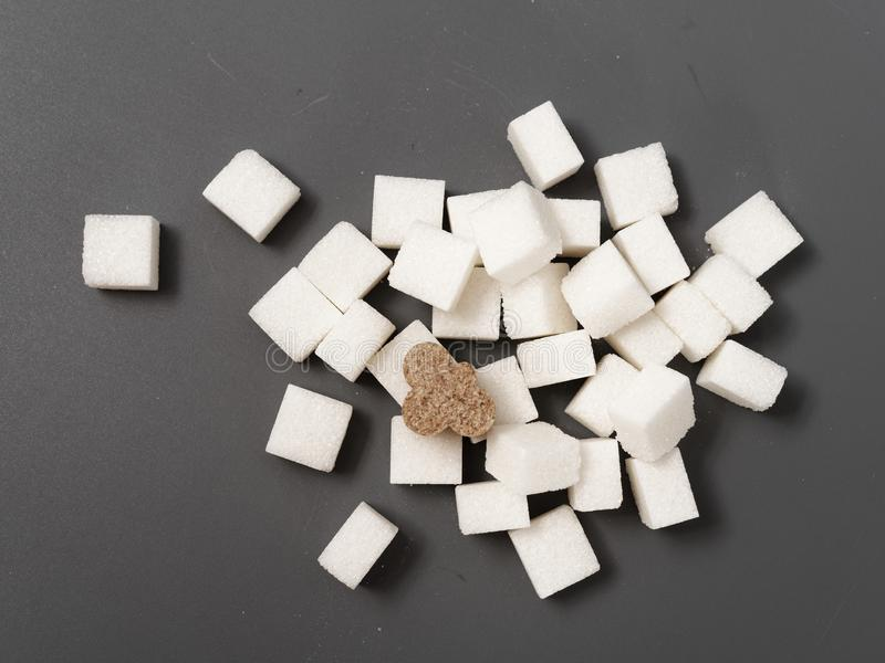 Refined sugar lump white and cane on a gray background. Refined white sugar cubes with stevia pills on grey background stock images