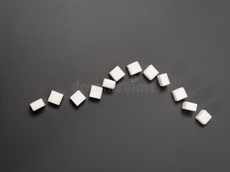 Refined sugar lump white and cane on a gray background. Refined white sugar cubes with stevia pills on grey background stock photos