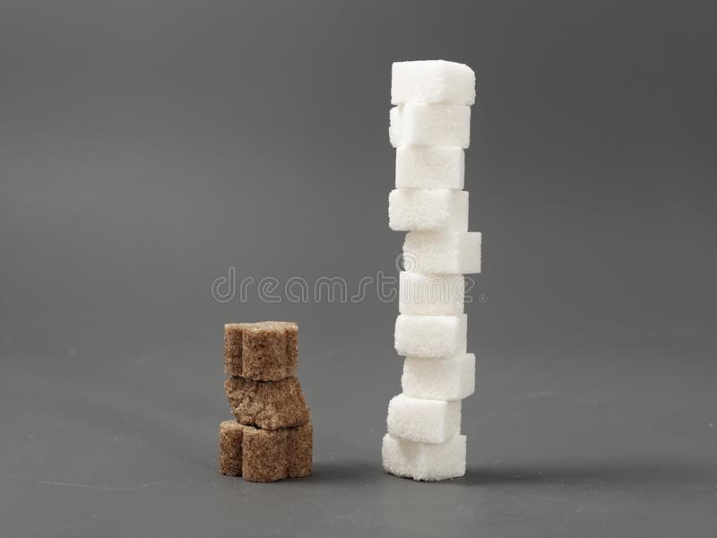 Refined sugar lump white and cane on a gray background. Refined white sugar cubes with stevia pills on grey background royalty free stock images