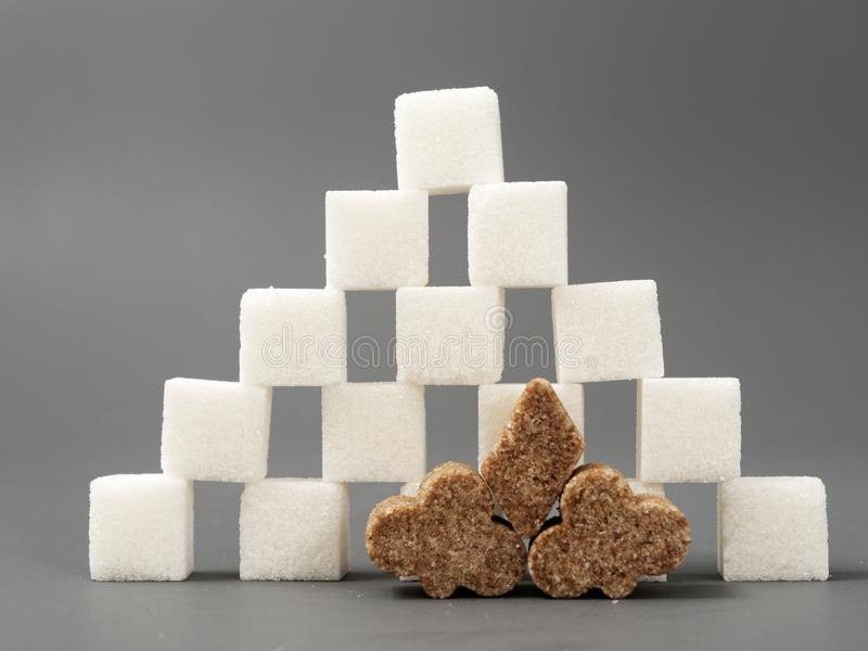 Refined sugar lump white and cane on a gray background. Refined white sugar cubes with stevia pills on grey background stock photo