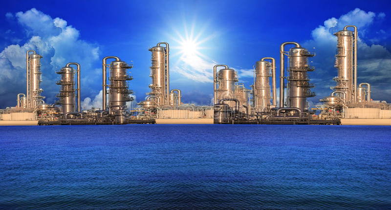 Refinery factory in industry estate. Beside sea with blue sky and sun shining royalty free stock photos