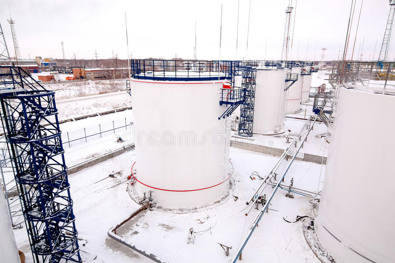 Refinery factory oil storage tanks under cloudy sky. Refinery factory oil storage tanks outside at winter under cloudy sky royalty free stock photography