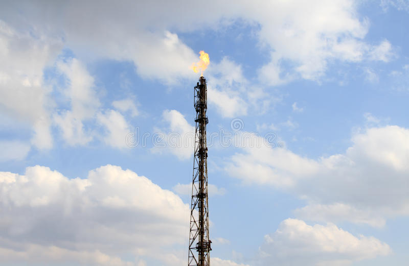 Refinery fire gas torch over sky royalty free stock photo